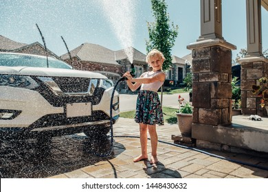 Cute preschool little Caucasian girl washing car on driveway in front house on sunny summer day. Kids home errands duty chores responsibility concept. Child playing with hose spraying water.
