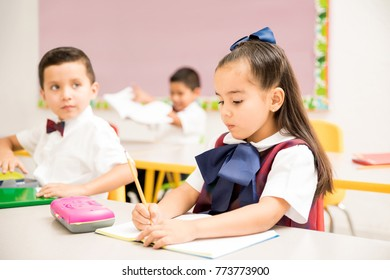 Cute preschool students wearing a uniform and doing a writing assigment in a classroom