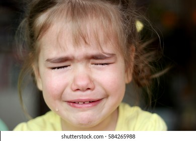 Cute preschooler blond girl crying with closed eyes over dark background, emotional closeup portrait, upbringing and family concept