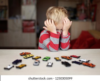 Cute preschooler boy playing with plenty of toy cars, creativity or materialistic demand, all he wants or negative emotions
