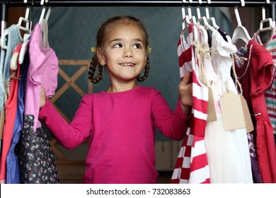 Cute preschooler girl has chosen a new lovely dress among a lot of clothes in child fashion store; she is happy. Sale, gifts, Christmas, holidays; beauty concept, place for your brand on tag