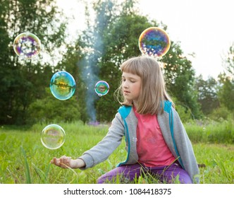 Cute preschooler girl playing with soap bubbles sitting in a summer park