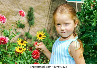 Cute preschooler girl portrait with natural flowers in the garden