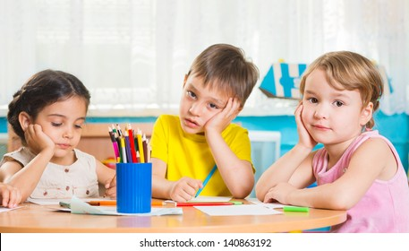 Cute preschoolers drawing with colorful pencils at daycare