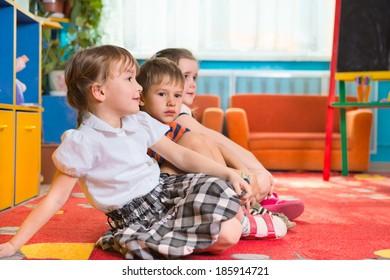 Cute preschoolers sitting on floor and listening to tutor