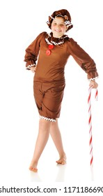 A cute preteen gingerbread girl leaning on a giant candy cane.  Isolated on white.