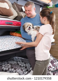 Cute preteen girl with father choosing accessories for their puppy in petshop