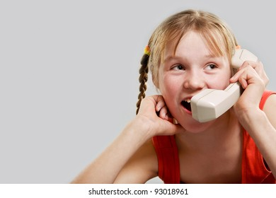 Cute preteen girl talking by phone receiver