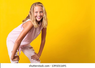 a69459115b59 Cute pre-teen girl wearing fashion summer clothes posing on yellow  background. 10 years
