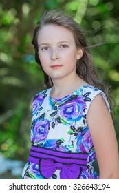 Cute preteen long hair girl posing on natural green background