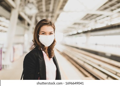 Cute pretty Asian female in a black suit wearing medical hygiene protective mask standing alone waiting for train at station. Concept for businesspeople prevents health from coronavirus or COVID-19.