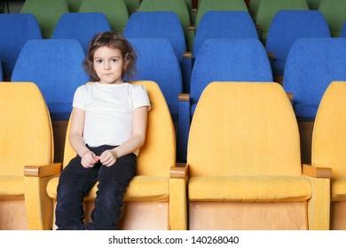 cute pretty emotional little girl in the cinema hall