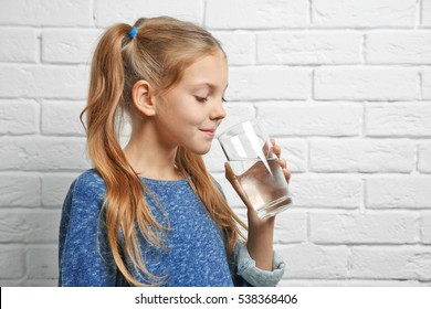Cute pretty girl with glass of water near brick wall