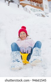 Cute pretty girl in red hat riding on a sled near the Austrian cottage