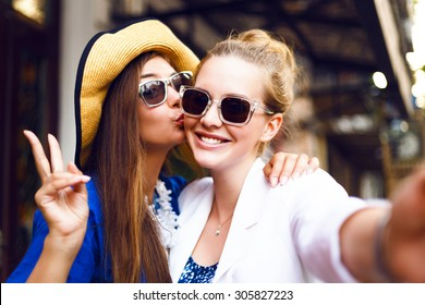 Cute pretty girls making funny selfie on the street, kissing to the cheek, having fun together,  joy, positive, love, friendship, sisters.