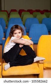 cute pretty little girl sitting in the cinema hall
