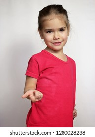 Cute pretty preschool girl in red t-shirt counting with fingers on the hand over white background, child emotional portrait, indoor closeup