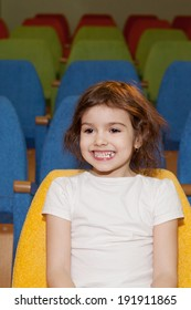 cute pretty smiling little girl sitting in the cinema hall