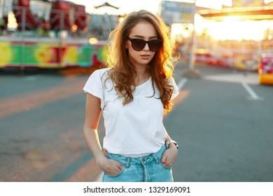 Cute pretty stylish hipster young woman in vintage jeans in fashionable sunglasses in a white stylish t-shirt walks and enjoys a sunny summer day in an amusement park. Nice girl model on vacation.