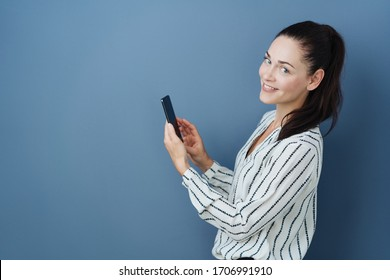 Cute pretty stylish young woman turning to the camera with a smile as she holds a mobile phone posing over a blue studio background