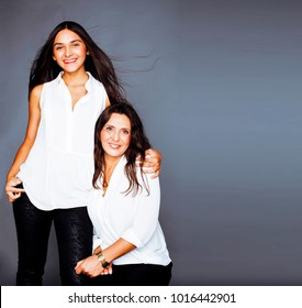 cute pretty teen daughter with mature mother hugging, fashion style brunette
