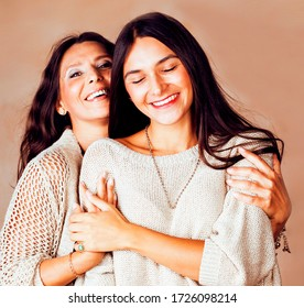 cute pretty teen daughter with mature mother hugging, fashion style brunette makeup together, warm colors