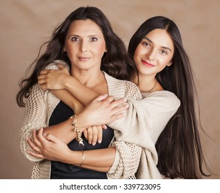 cute pretty teen daughter with mature mother hugging, fashion style brunette makeup close up tann mulattos