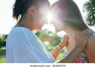 Cute pretty teen daughter with mature mother hugging in nature at sunset