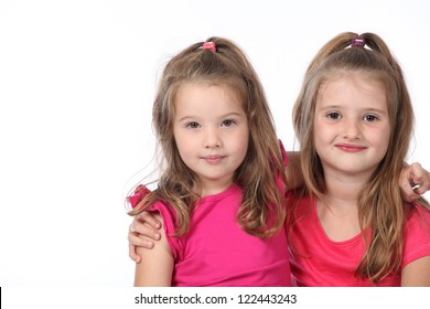 Cute and pretty twins and sisters having a photo shoot wearing jeans and pink t-shirts on a white seamless high key background