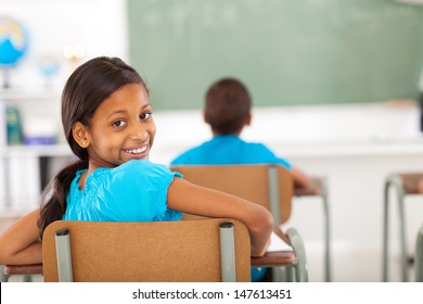 cute primary school girl in classroom looking back