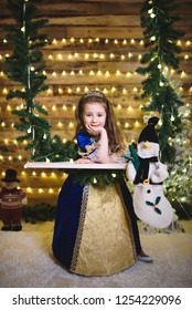 cute princess at seesaw with snowman at christmas studio