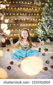 cute princess sitting on white carpet in christmas lights