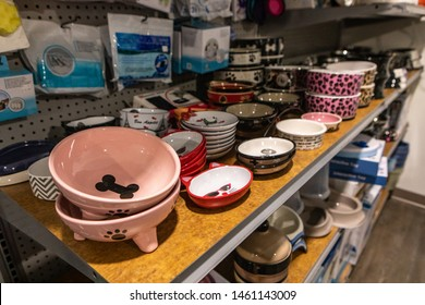 Cute products inside a pet superstore. A close up view on ceramic pet bowls on the shelves of a pet store. Various sizes and patterns are seen for cat feeding, with copy space on the right.