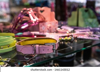Cute products inside a pet superstore. A closeup view of a stylish pink leather pet collar with crystal clasp, on a shelf inside an animal store, colorful accessories are seen blurry in background.