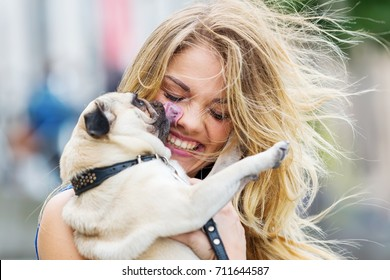 cute pug licks the face of a pretty woman