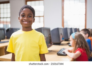 Cute pupil in computer class smiling at camera at the elementary school