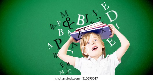 Cute pupil holding books against green