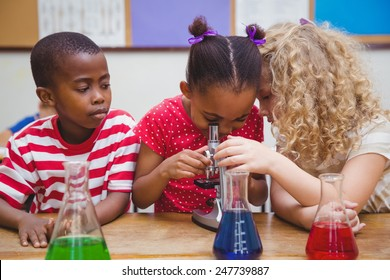 Cute pupil looking through microscope at the elementary school