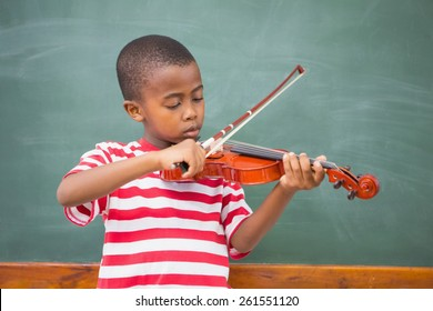Cute pupil playing violin in classroom at the elementary school