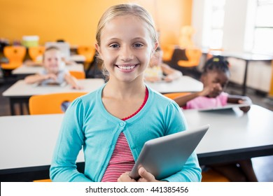 A cute pupil posing with tablet pc in classroom