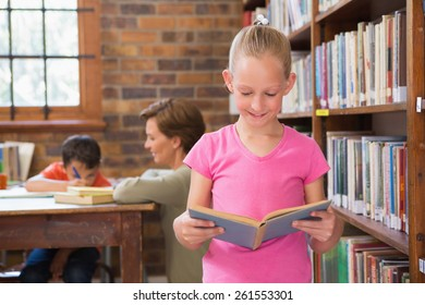Cute pupil reading in library at elementary school