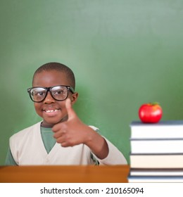 Cute pupil showing thumbs up against red apple on pile of books