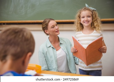 Cute pupil smiling at camera during class presentation at the elementary school