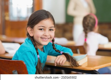 Cute pupil smiling at camera at her desk in classroom at the elementary school