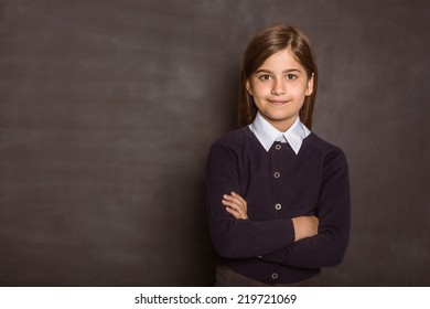 Cute pupil smiling at camera on black background