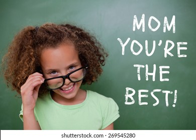 Cute pupil tilting glasses against green chalkboard