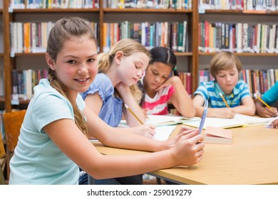 Cute pupil using tablet computer in library at the elementary school