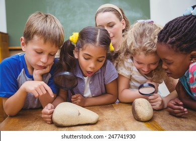 Cute pupils looking through magnifying glass at the elementary school