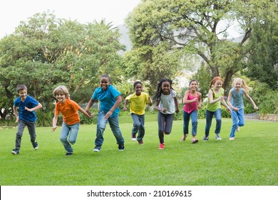 Cute pupils racing on the grass outside at the elementary school
