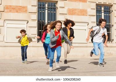 Cute pupils running  from school building